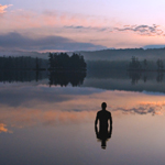 Silhouette of man standing in lake at sunrise