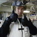 Photo of host David Pogue giving two thumbs up while wearing aircraft carrier flight deck gear