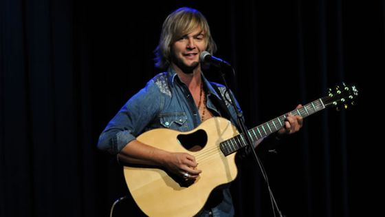 Image of Keith Harkin playing his guitar on stage