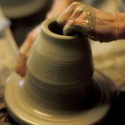 clay and hands on spinning wheel