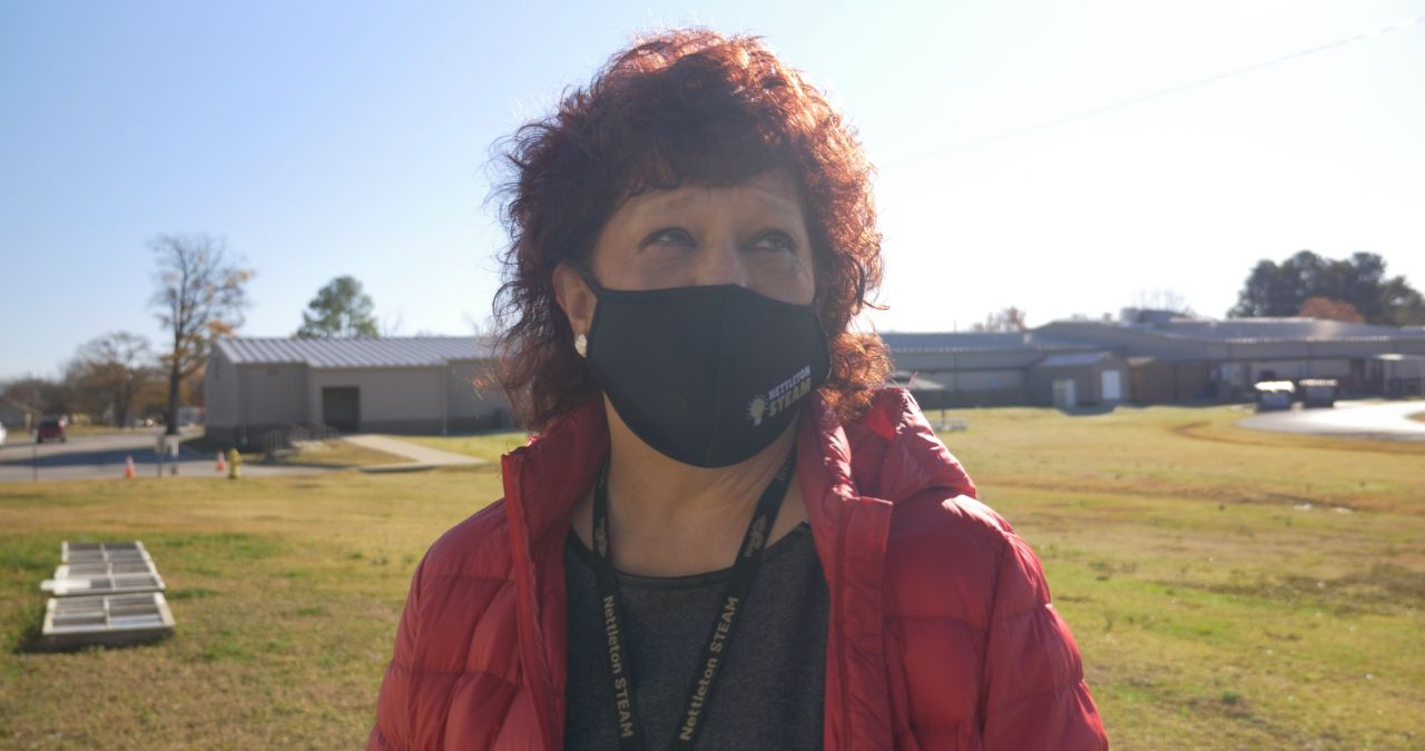 Masked, female Nettleton STEAM educator with red curly hair in a red jacket and grey shirt standing outside in front of school building