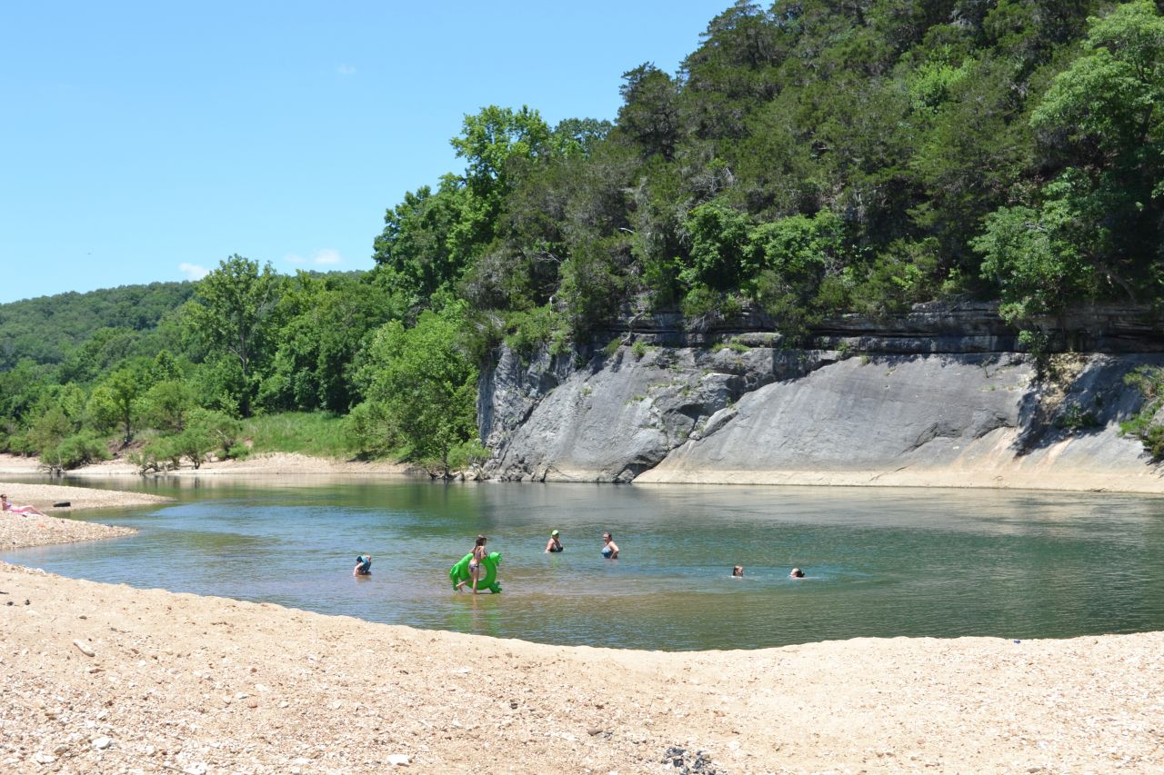 Shine Eye Swimming Hole - below a forested bluff line, swimmers stand and bob in the water while a young girl in a purple bathing suit wades in with a green frog inner tube. Along the shoreline in the foreground, a woman in her bathing suit sunbathes on a pink towel.
