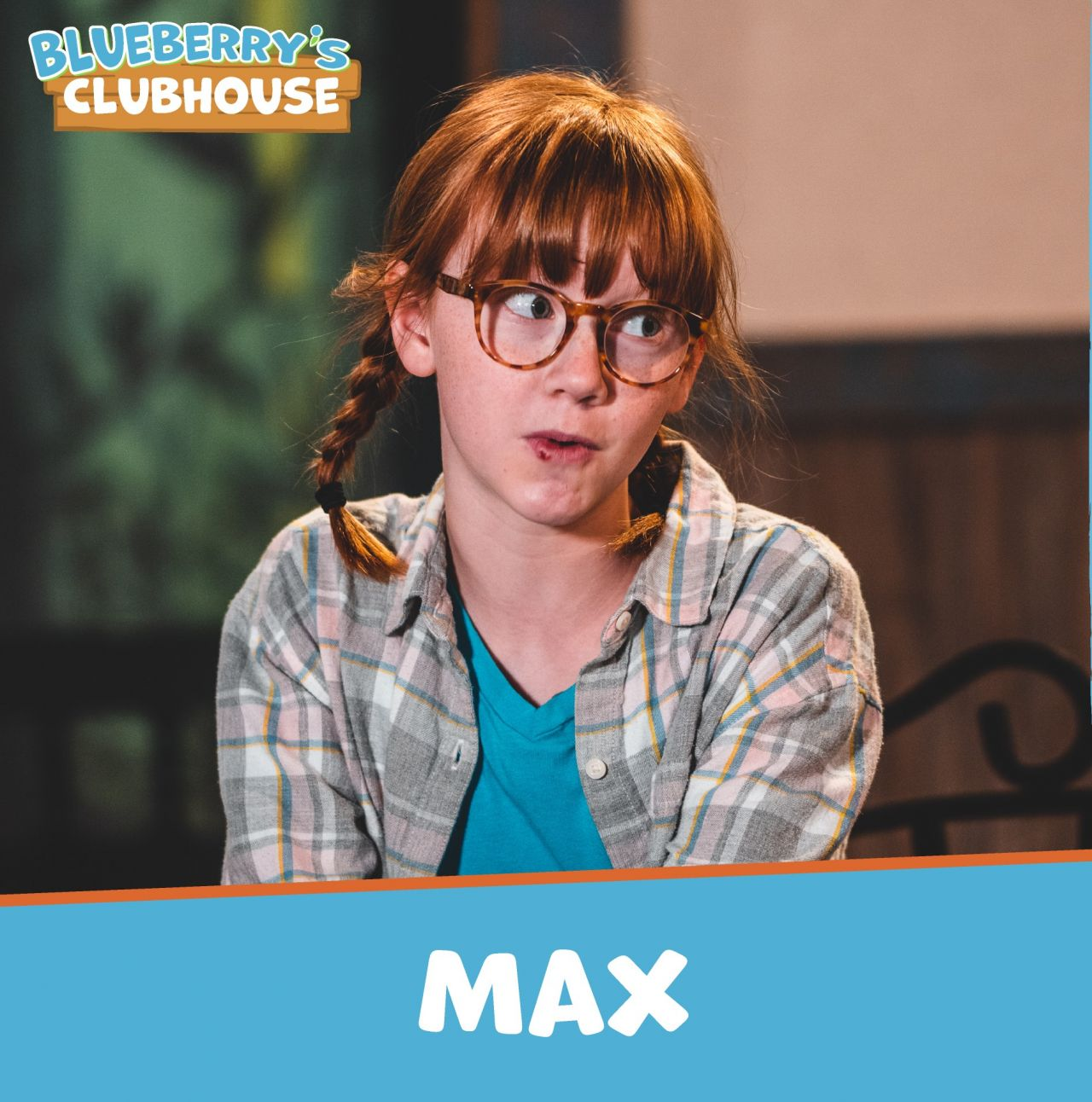 Max, with hair in pigtails and wearing a teal t-shirt under a grey, pink, blue, white and yellow plaid, long-sleeved button-down shirt and tortoiseshell glasses, casts a surprised glance to someone offscreen