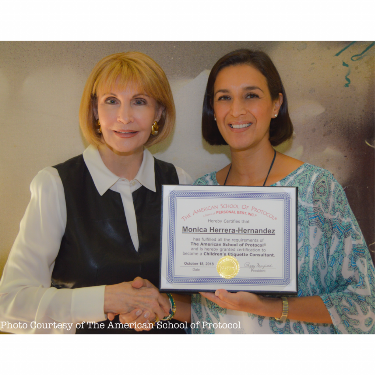Monica Herrera-Hernandez holds her American School of Protocol diploma while shaking the hand of organization president Peggy Mansfield
