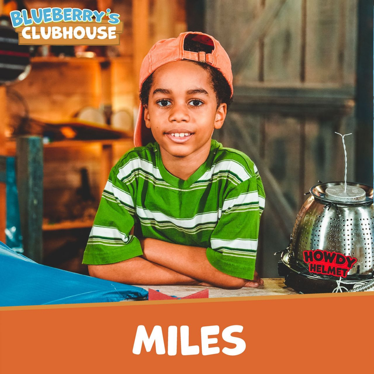 Miles, wearing an orange backwards baseball cap and green and white striped T-Shirt, looks into the camera with the Howdy Helmet sitting on the counter to his left