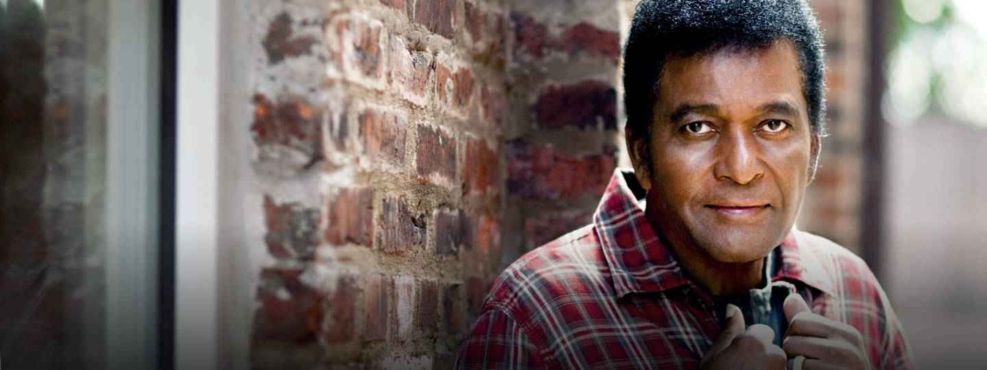 Charley Pride standing against brick building outdoors