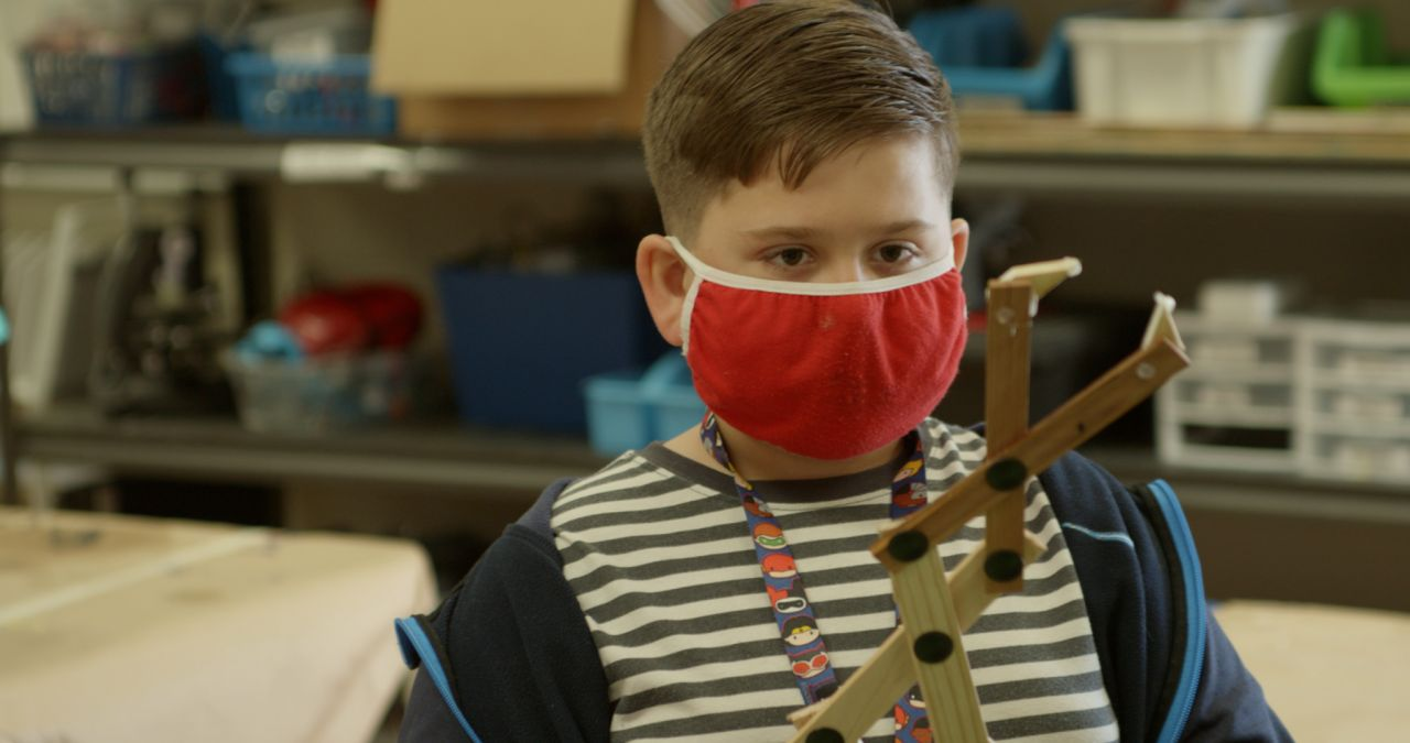 Young, white, brunette boy in a mask operates a mechanical arm in a Nettleton STEAM classroom
