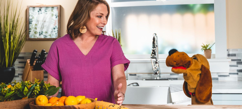 Una mujer con una camisa rosa habla con un títere de perro en una cocina