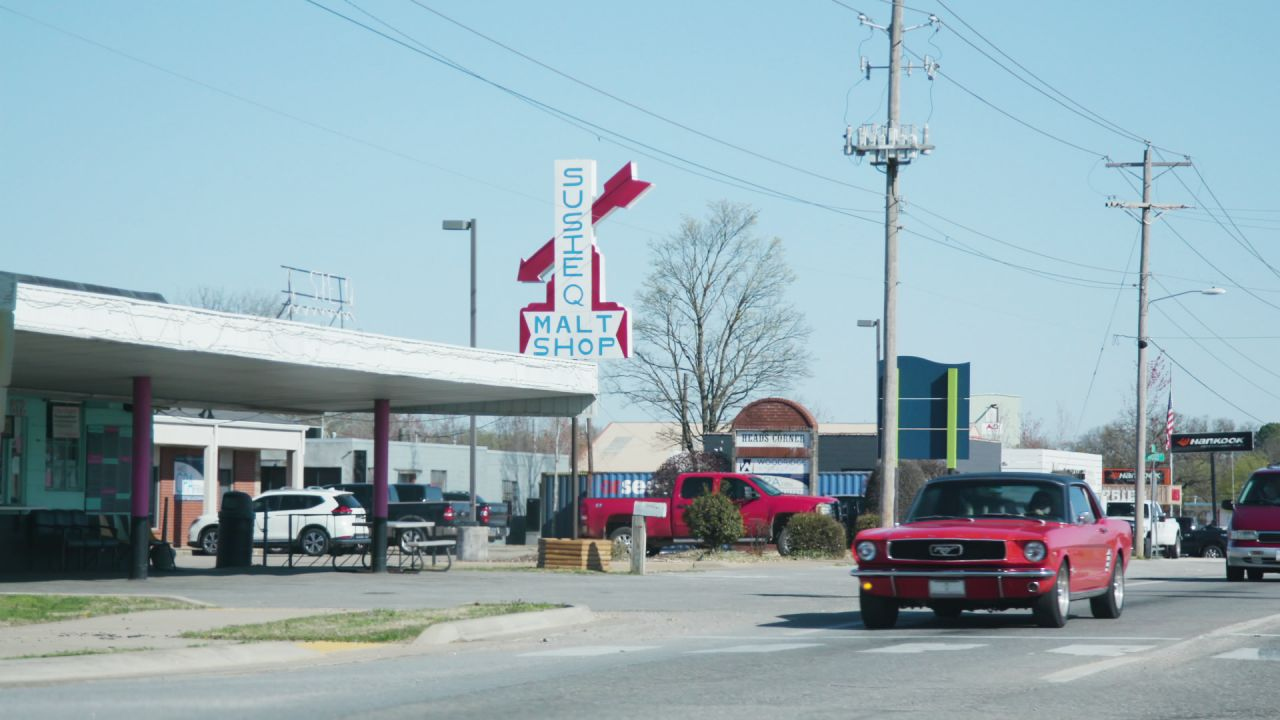 A classic, red and black Ford Mustang drives past the Susie Q Malt Shop sign