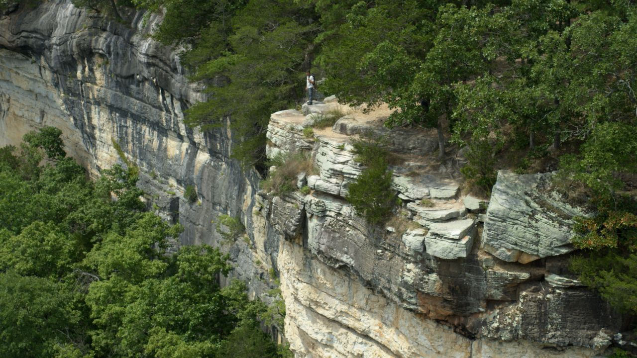 Aerial view of Chuck Dovish, wearing a white polo, grey hiking pants and hiking books and carrying a dark-colored backpack, standing atop the bluffs of the Kings River Overlook