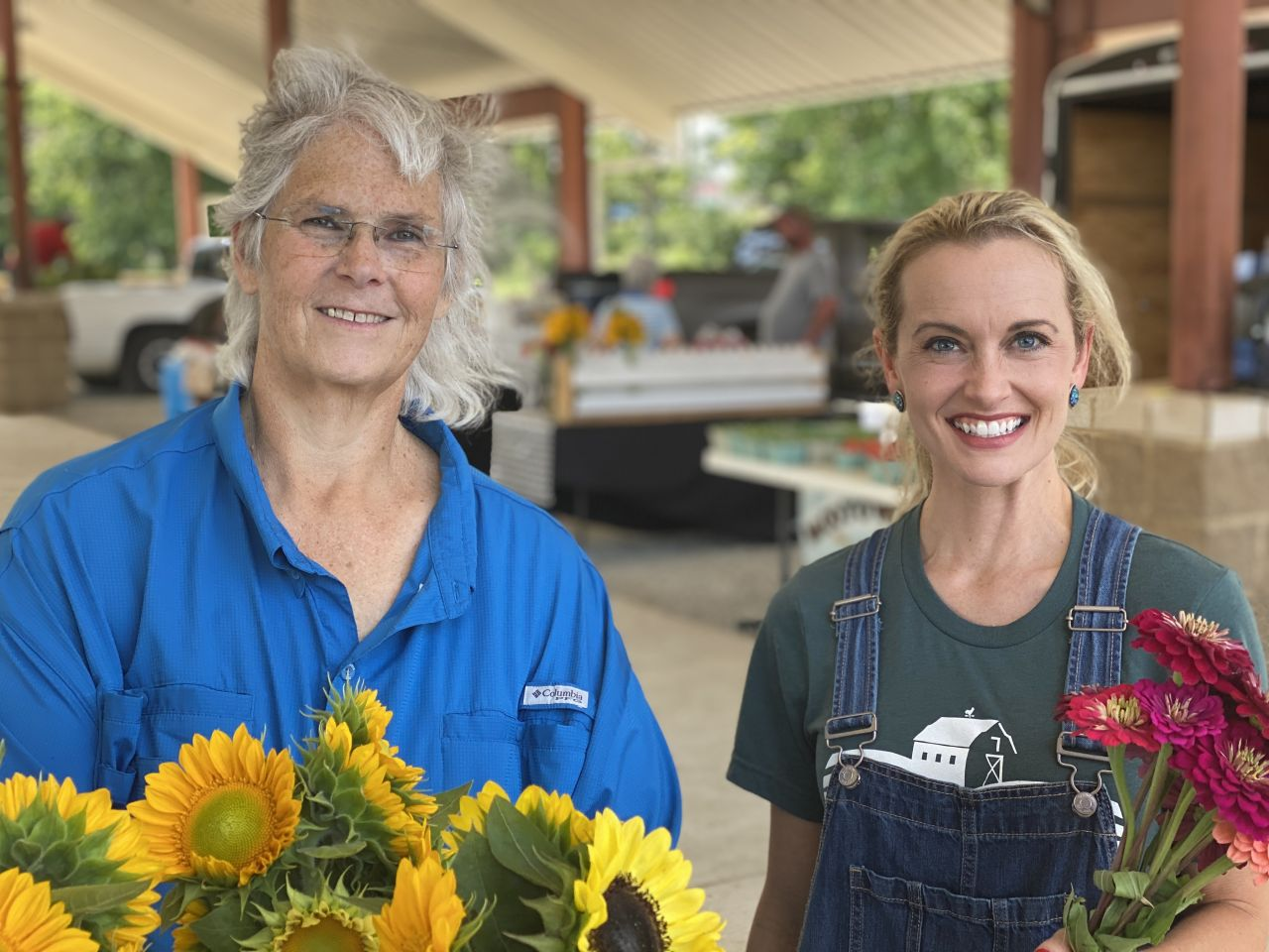Dr. Kim Pittcock and Good Roots Hosts Lauren McCullough, holding a bunch of fresh zinnias, stand together at the ASU Regional Farmers Market.