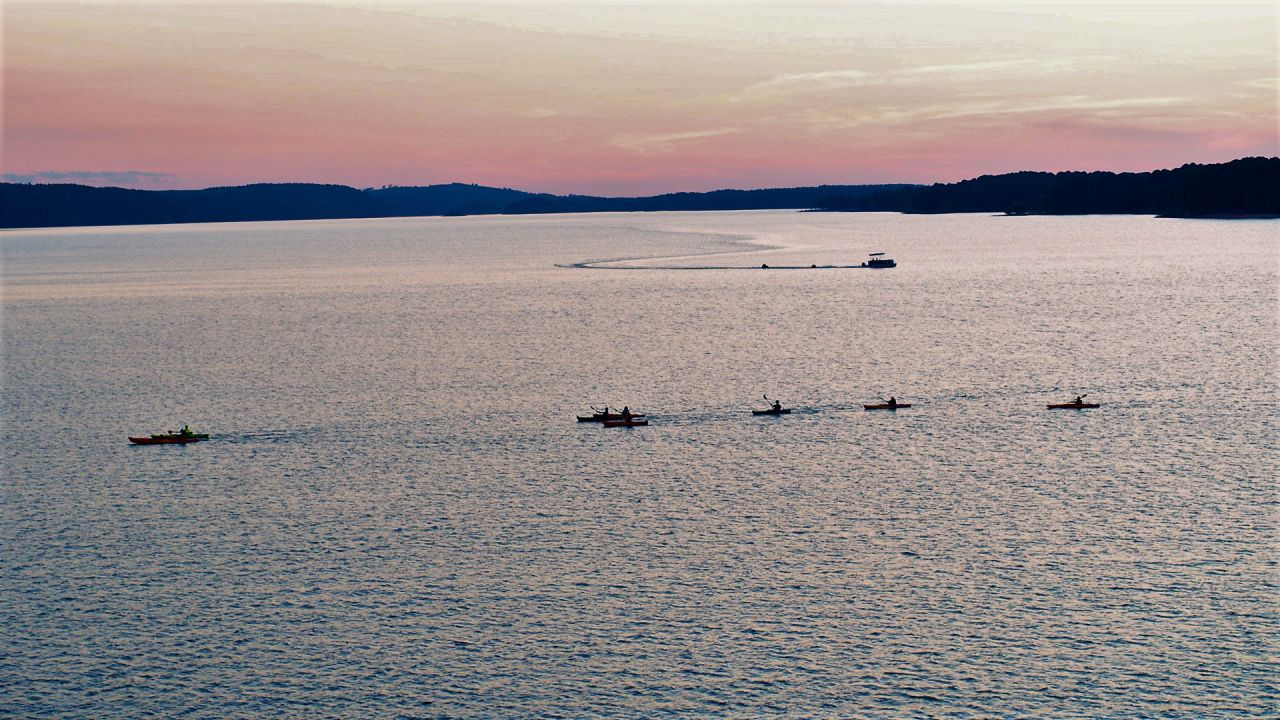 Seven kayakers paddle at sunset on Lake DeGray while a pontoon boat motors along in the background