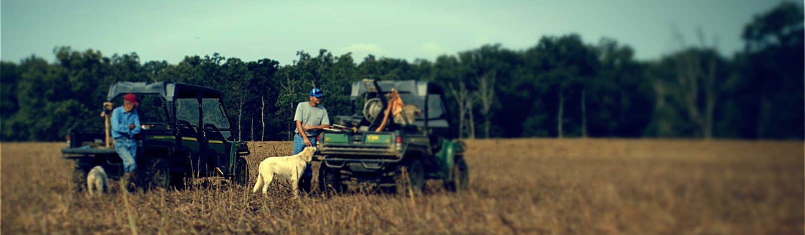 A couple of farmers and their dog in a field