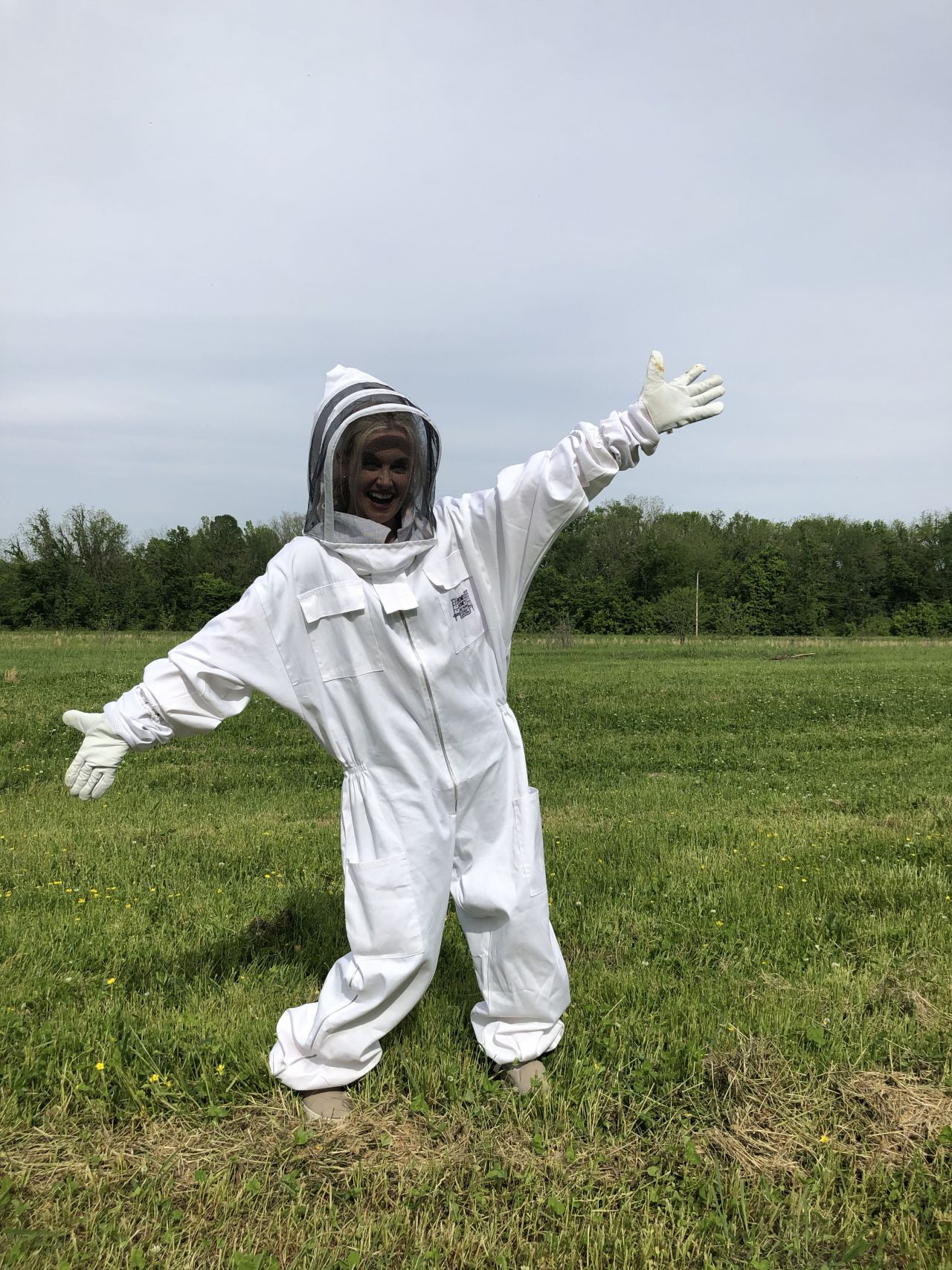 Lauren McCullough poses in field in full beekeeping attire