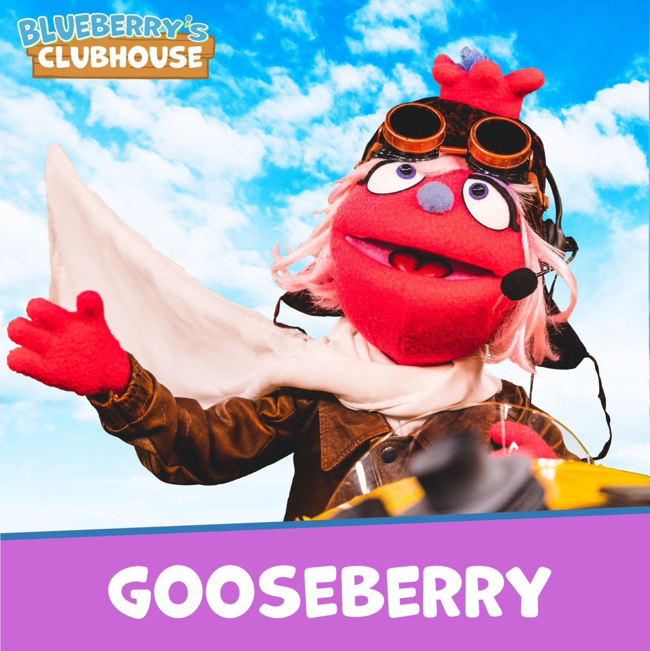 Boysenberry, wearing an aviator jacket, scarf and googles, as well as headset with speaker, waves to the camera