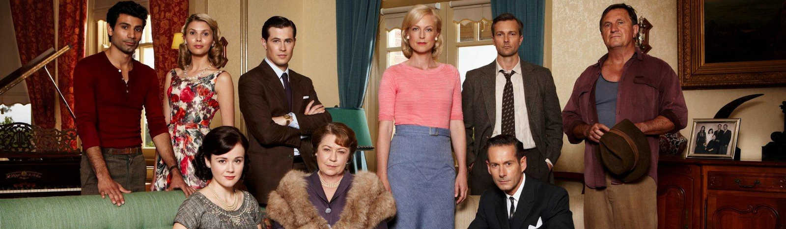 The cast lined up in a living room