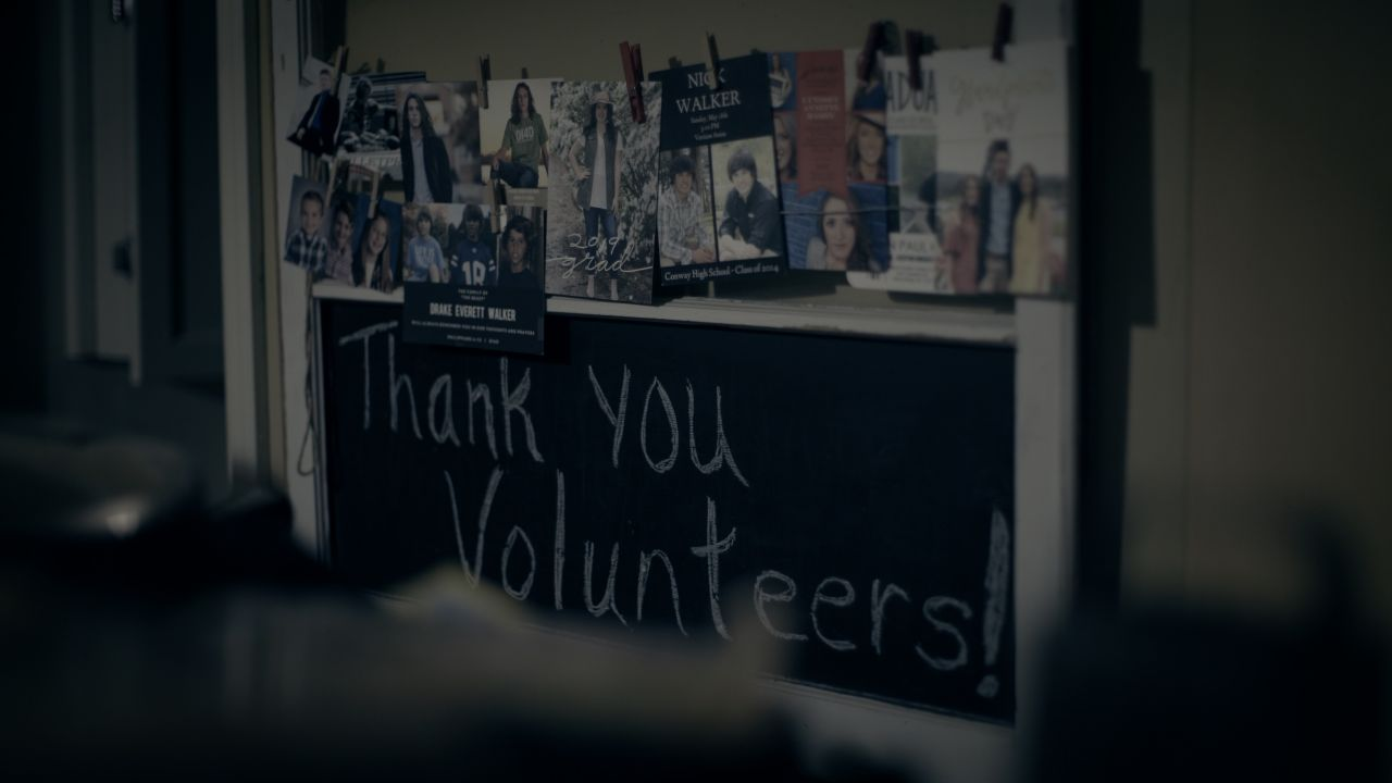 """A chalkboard reading, """"Thank You, Volunteers!"""" is displayed in the Plouch home."""