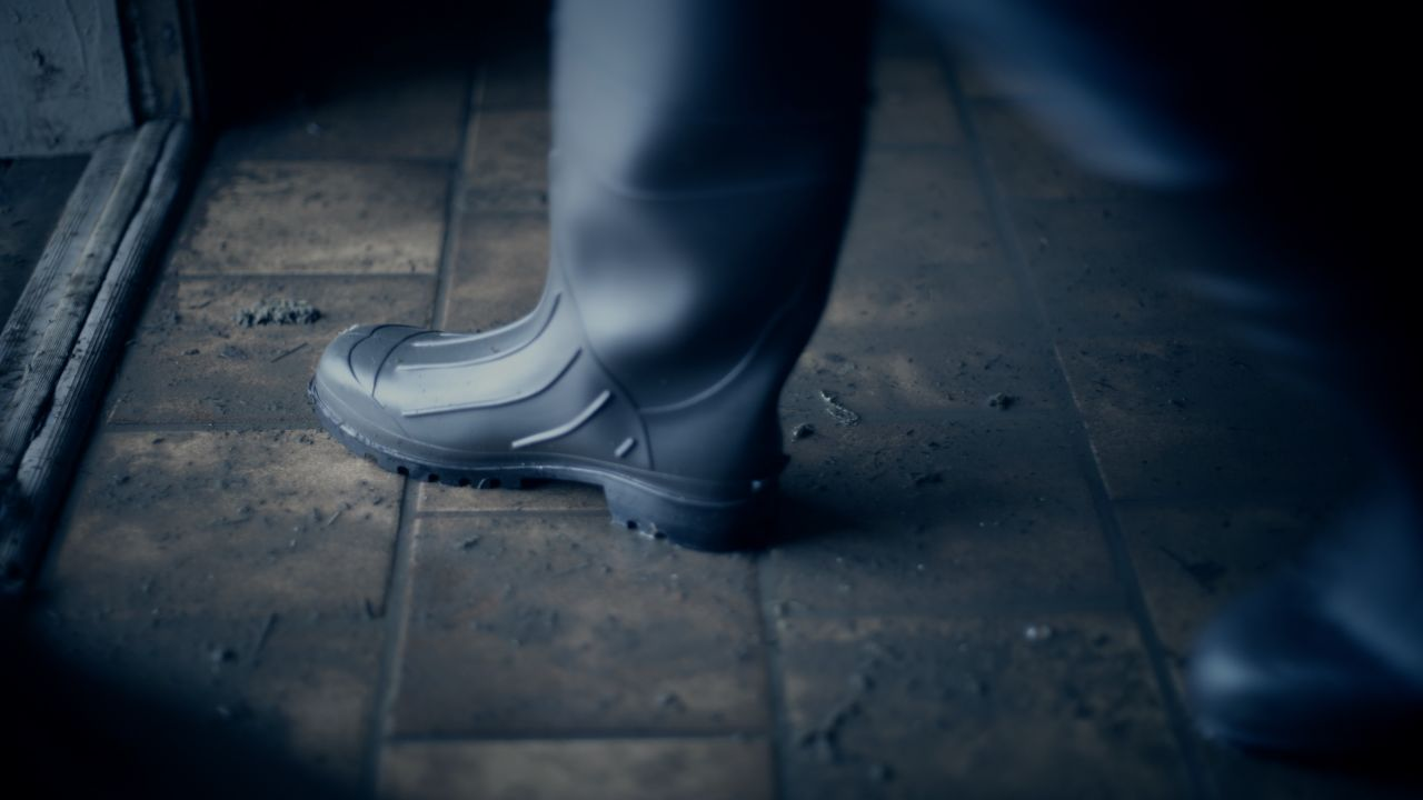 A booted foot trudges through the sludge left behind on the floor of a Treasure Hills home after the flood has receded.