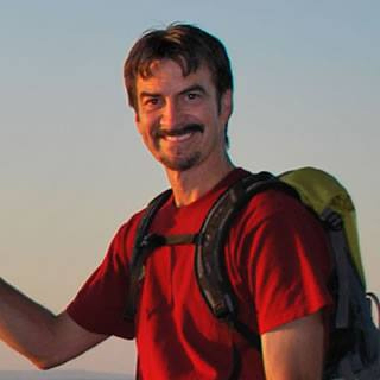 Headshot of Chuck Dovish outfitted in backpacking gear and a red T-shirt