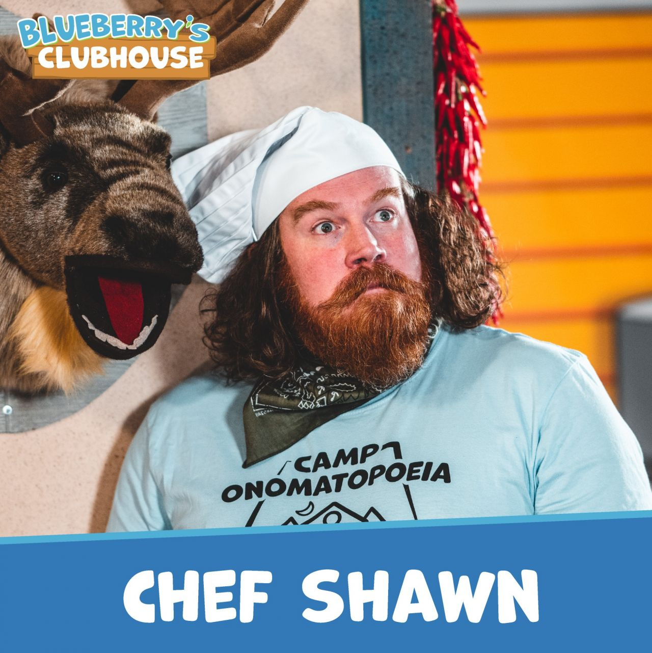 Chef Shawn, in light blue Camp Onomatopoeia, black bandana, and white toque, stands next to Mere the Moose in the mess hall