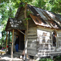 Man standing on porch of old cabin