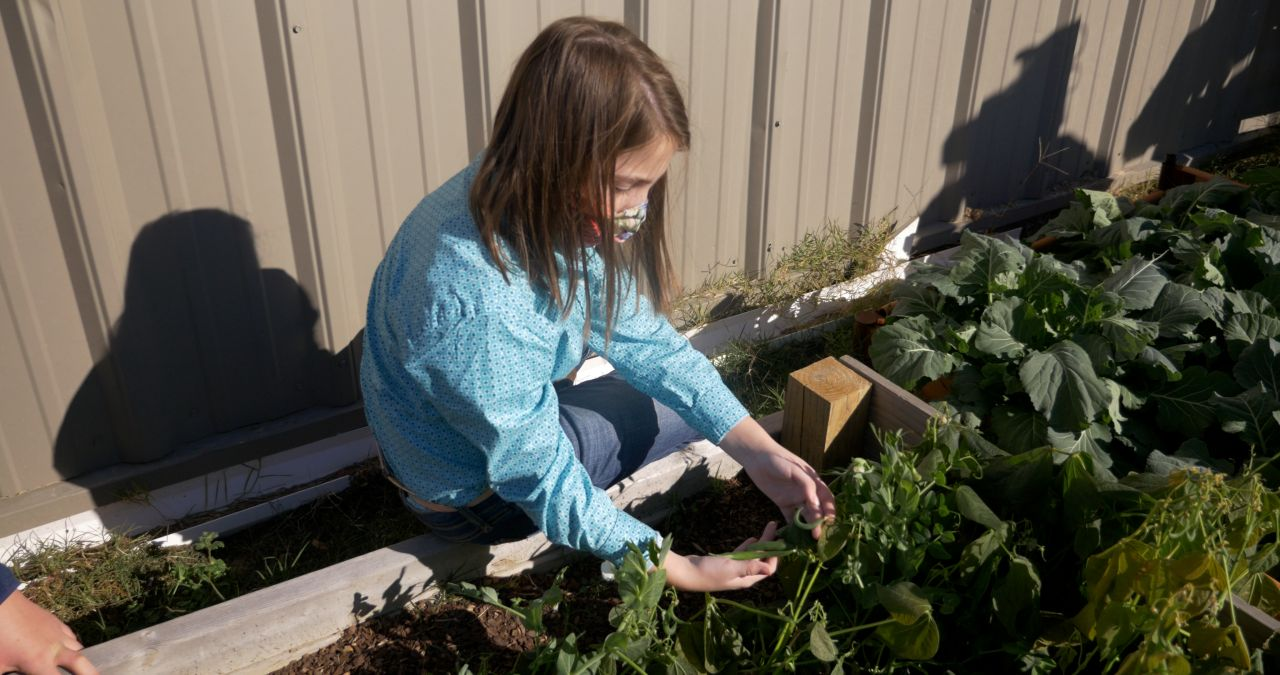 Nettleton STEAM student, a young brunette girl with mask, in garden