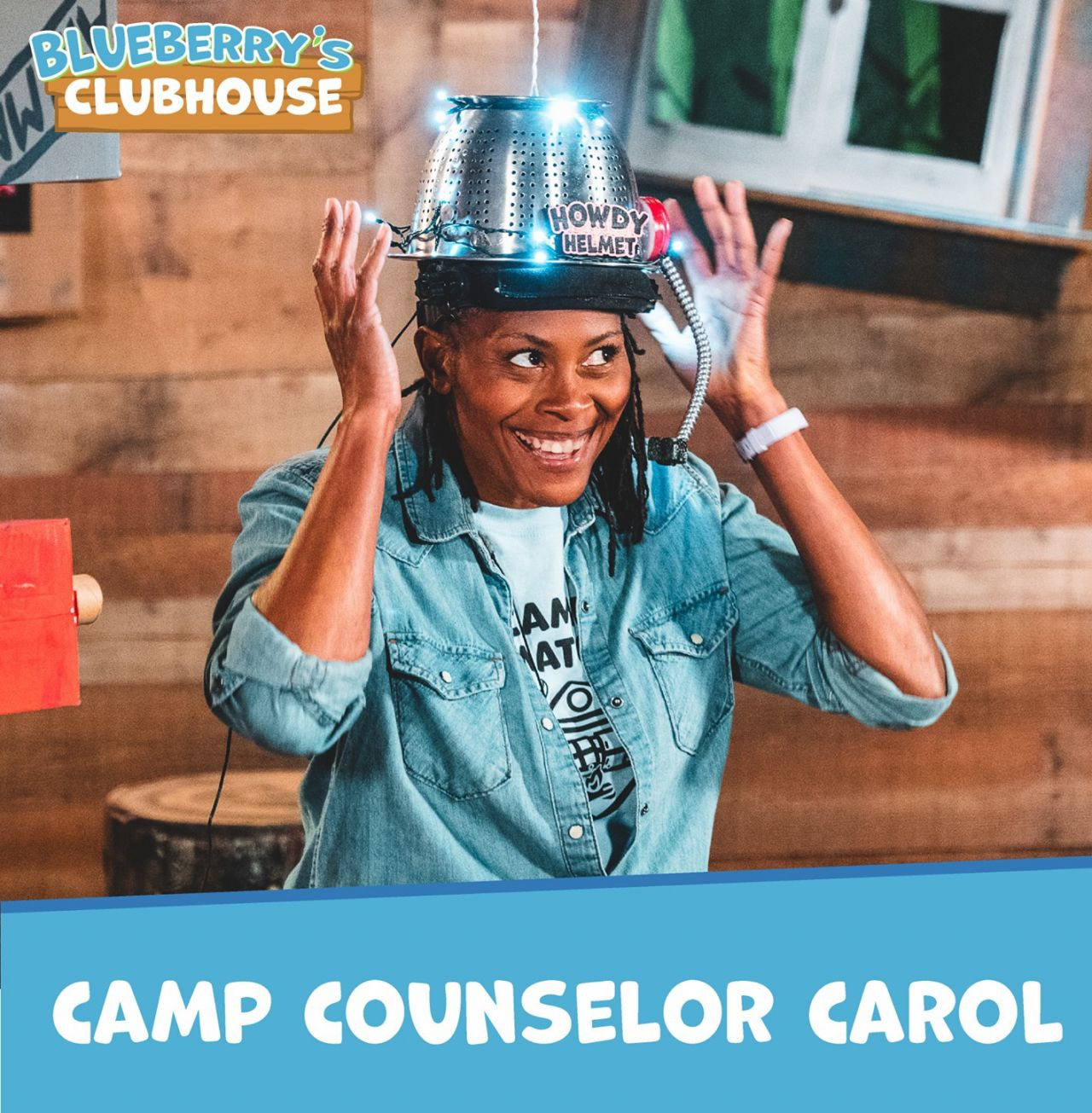Camp Counselor Carol, wearing a light blue Camp Onomatopoeia T-shirt under a denim, long-sleeved snap-front shirt tries on the Howdy Helmet, which resembles a colonnade with lights and headset