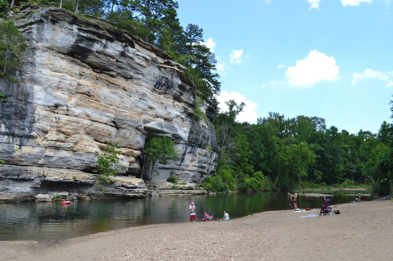 Ozark Campground Swimming Area - families play in shallow water and along the shoreline of a river in front of a forested bluff.