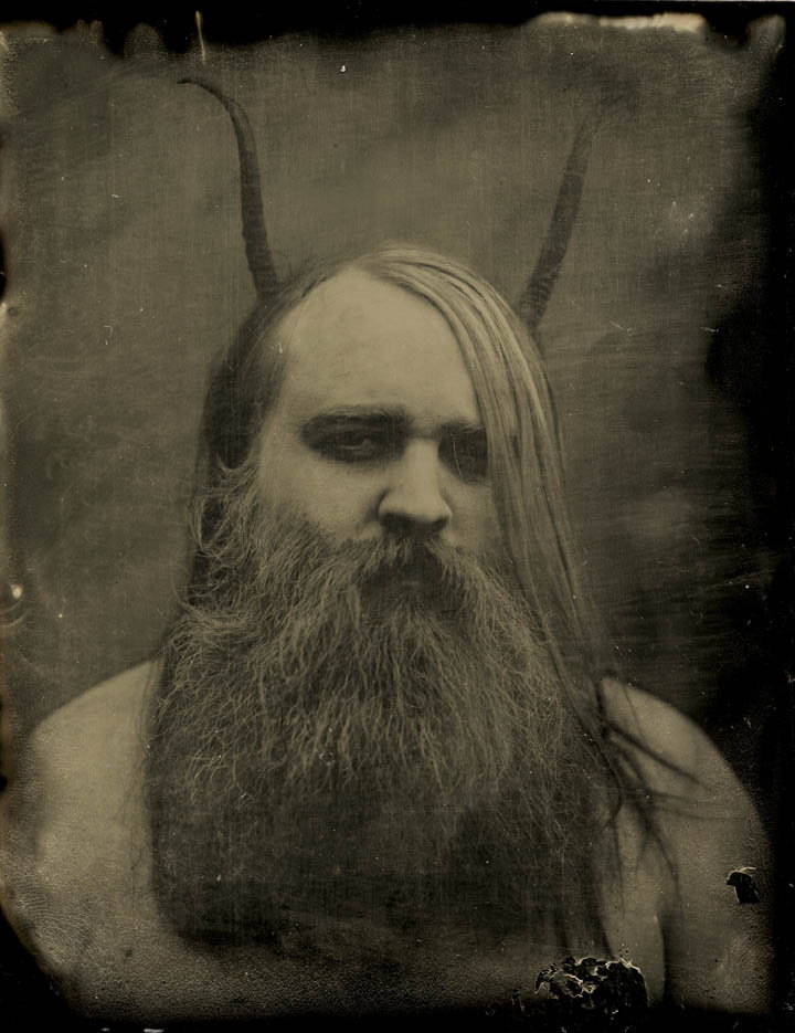 Worn photo of bearded man with horns