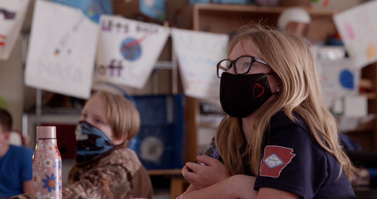 Young blonde girl in mask and glasses and young blonde boy in gaiter and camo jacket sit in Nettleton STEAM classroom with shelf with NASA projects in the background