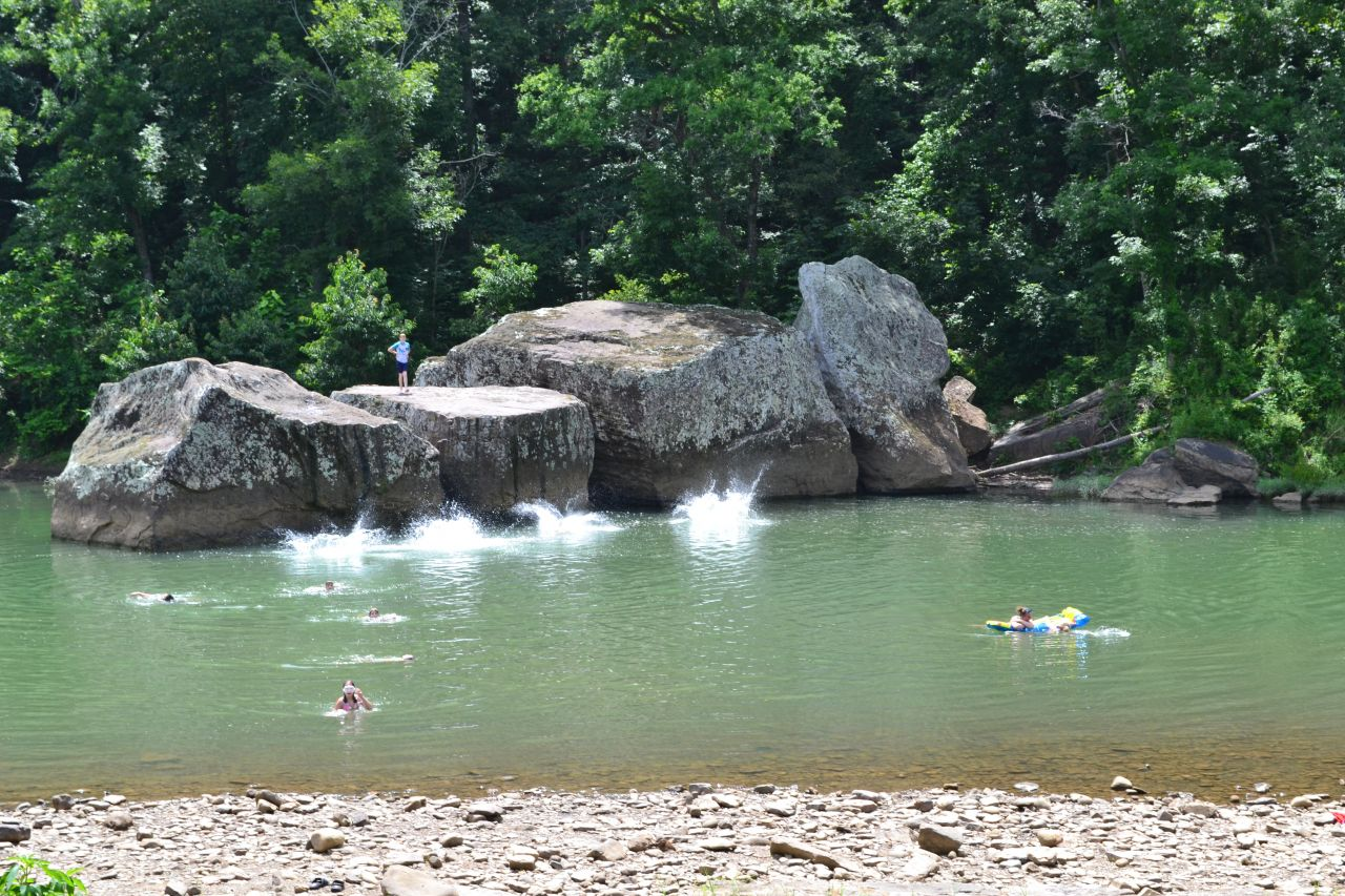 Large boulders loom out of the Long Pool Swimming Area against a forested background. A child in swimming gear stands atop one rock while the splashes from jumpers are suspended mid-air and other children swim to the shoreline. To the left, a mother and child swim with a raft float.