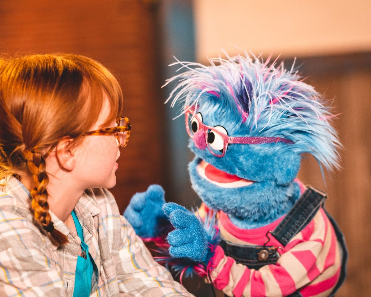 Max, in a brown plaid button down over a turquoise tee, looks at Blueberry - dressed in a long-sleeved pink and gray striped top under denim overalls, who is talking and gesturing excitedly.