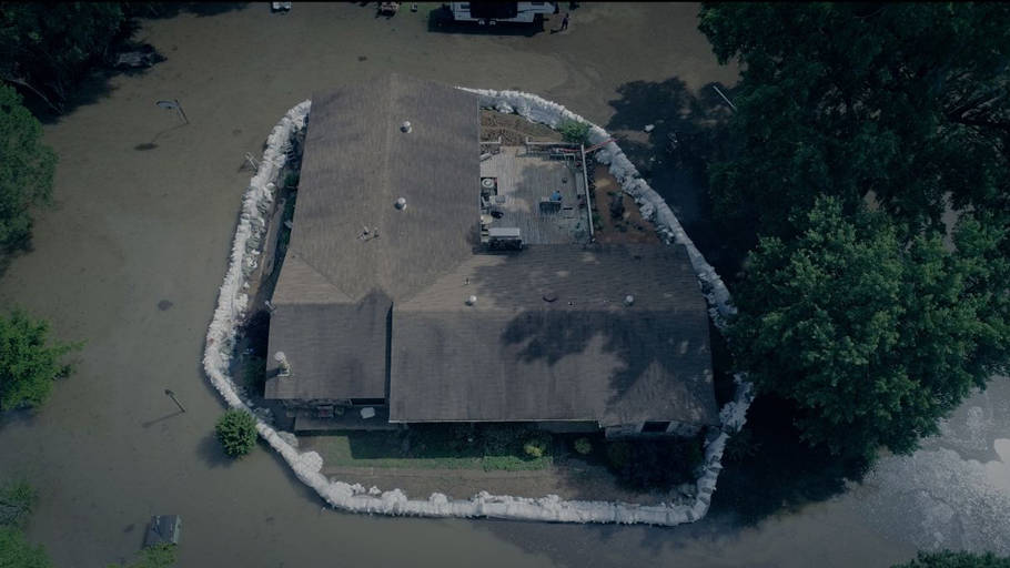 arial photo of home surrounded by flood waters and sand bags