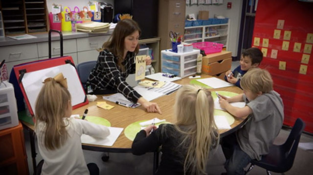 Teacher doing phonetic activities with students at desk