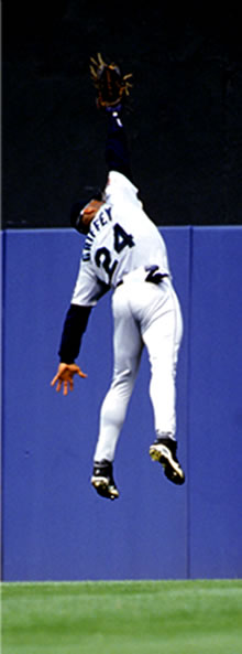 Image of baseball player jumping to catch a baseball