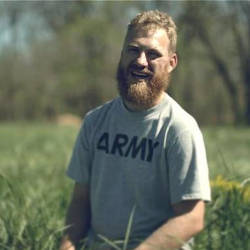 Smiling man in field with Army Shirt