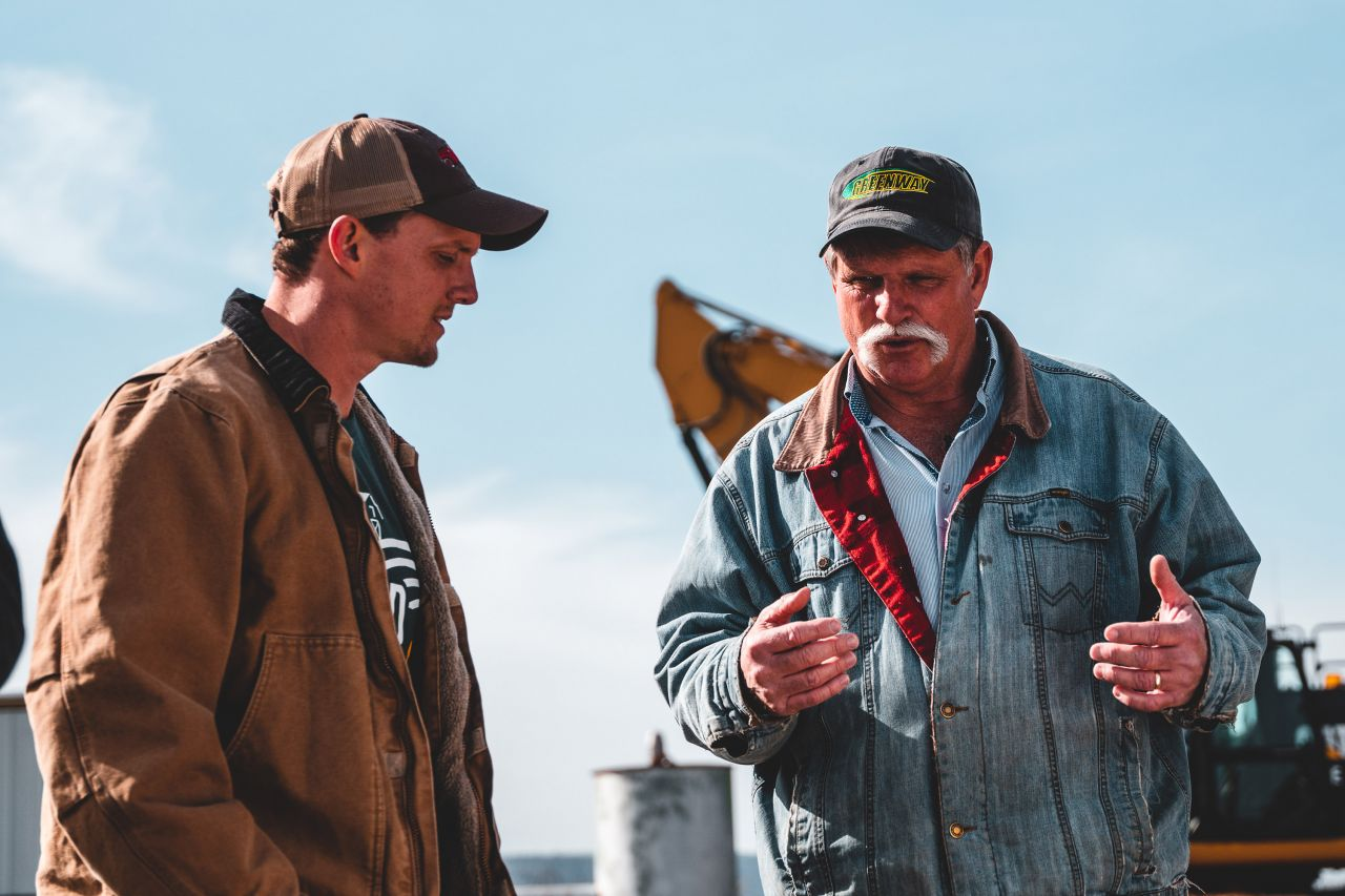 DuVall and Ralston talking together on farm