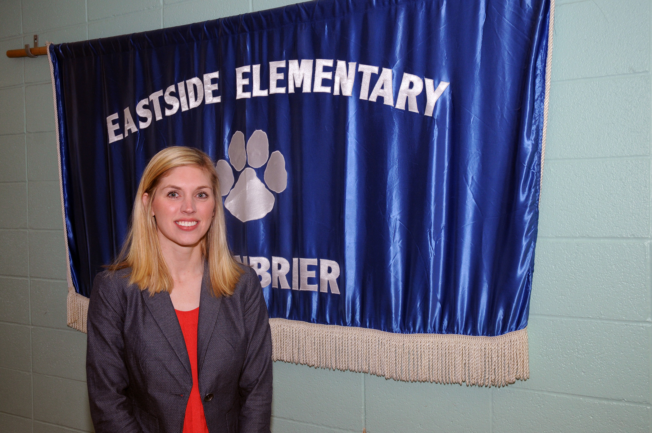 Sarah Jerry standing in front of elementary school banner