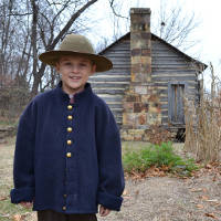 boy in period clothes in front of old shack