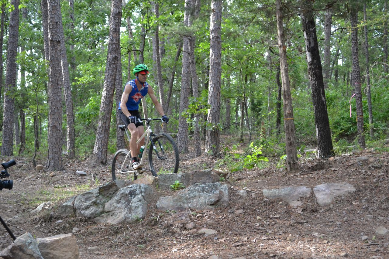 A cyclists rides down the Iron Mountain Trail along Lake DeGray