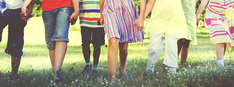 Children holding hands while walking through field.