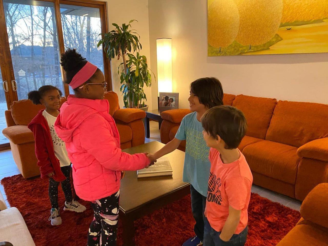 Two young African American girls in athletic gear and coats and two hispanic boys in jeans and t-shirts demonstrate handshaking and introduction in a colorful family living room
