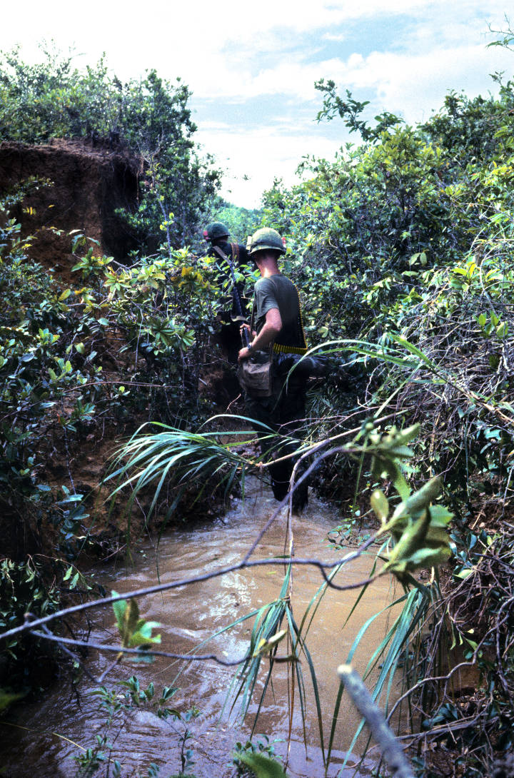 Soldiers search for trip wires in the ditch